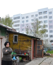 """3/10 """"Unser Haus ist mehr als 100 Jahre alt, aber wir haben hier eigentlich alles"""" sagte die Bewohnerin einer der Holzhütten im Schatten einer modernen Wohnanlage """"sogar fast immer Strom!"""" Die Siedlung am Rande der Stadt Yaroslavl, 250km nordöstlich von Moskau, besteht aus Holz- und Lehmhütten, wie sie im dörflichen Russland seit Jahrhunderten gebaut werden. Die Straßen sind nicht asphaltiert und Trinkwasser wird von öffentlichen Brunnen geholt."""
